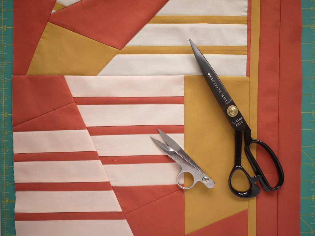 Improv (ignore the scissors in this photo!): Three slabs joined together - rectangle with yellow stripes at top, rectangle at the bottom with peach stripes, three longs strips at the right.